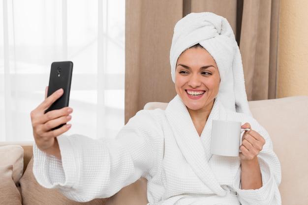 Frau, die selfie im hotelzimmer nimmt