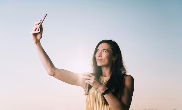 Frau, die selfie im sonnenlicht nimmt