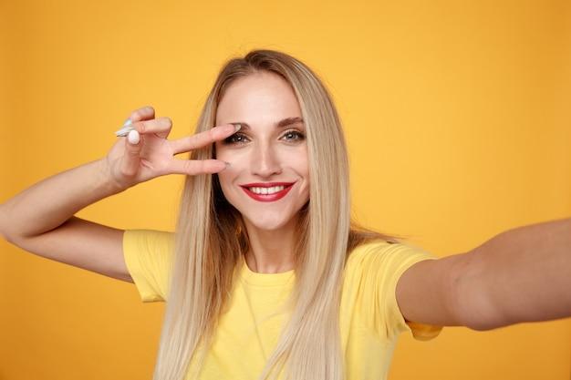 Frau, die selfie macht und spaß im gelben hintergrund hat
