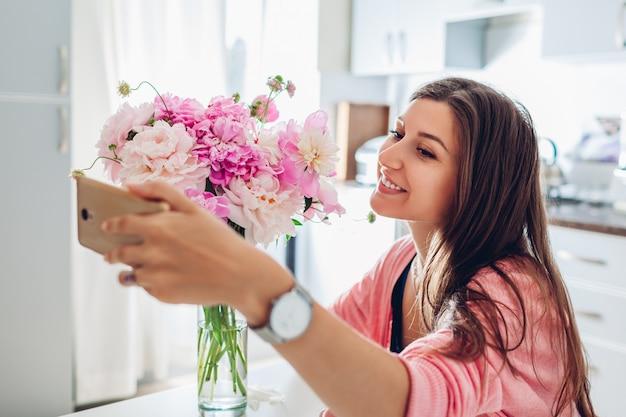 Frau, die selfie mit blumenstrauß von pfingstrosenblumen zu hause unter verwendung des smartphones nimmt.