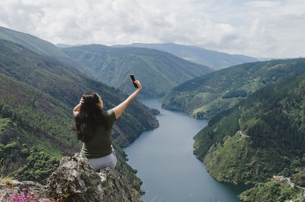 Frau, die selfie mit dem fluss nimmt