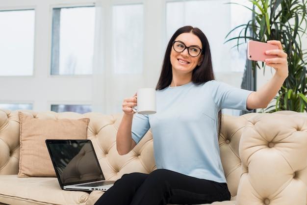 Frau, die selfie mit kaffee auf couch nimmt