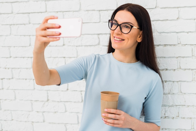 Frau, die selfie mit kaffeetasse nimmt