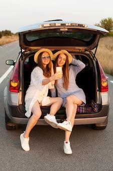 Frau, die selfie nimmt, während im autokofferraum