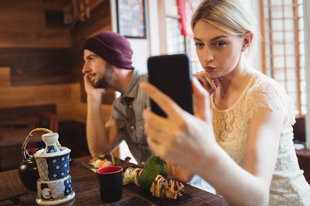 Frau, die selfie nimmt, während mann am telefon spricht