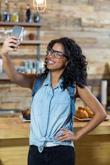 Frau, die selfie vom handy am schalter nimmt