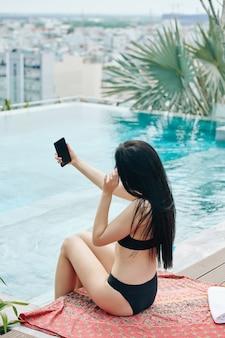 Frau, die selfies durch pool nimmt