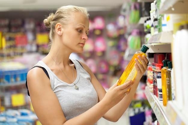 Frau, die shampooflasche im speicher betrachtet