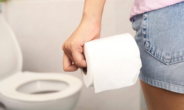 Frau, die shorts trägt und toilettenpapier im badezimmer hält