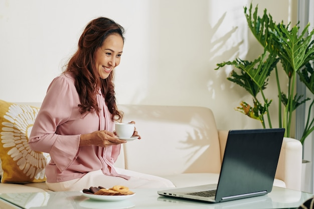 Frau, die show auf laptop beobachtet