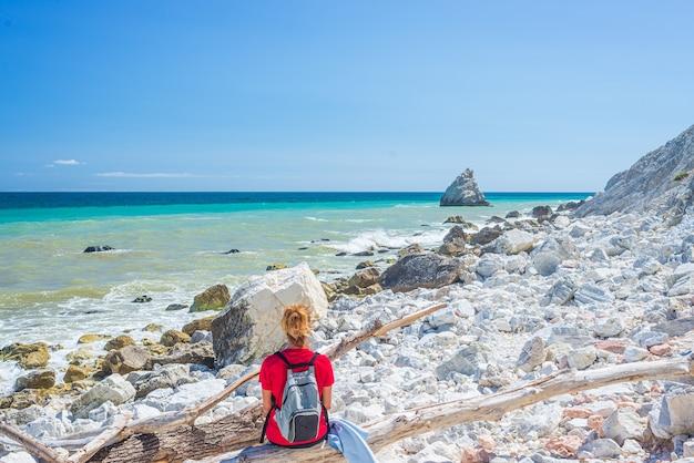 Frau, die sich am italienischen strand entspannt. ungleiche küste von conero, kiesstrand, türkisfarbenes wasser, echte menschen, rückansicht, sonniger tag, urlaub in italien