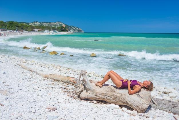 Frau, die sich am italienischen strand entspannt. ungleiche küste von conero, kiesstrand, türkisfarbenes wasser, echte menschen, seitenansicht, sonniger tag, urlaub in italien