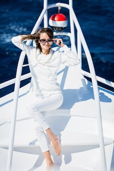 Frau, die sich an einem sonnigen sommertag auf see auf der nase der yacht entspannt und urlaub und luxusreisen genießt enjoying