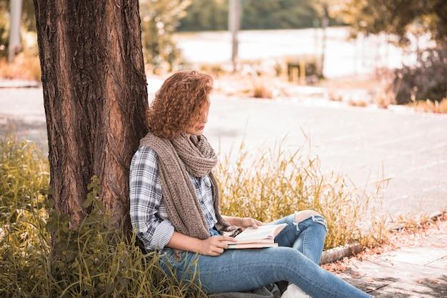 Frau, die sich auf baum lehnt und garten des buches öffentlich liest