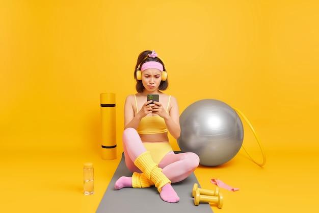Frau, die sich auf das smartphone-display konzentriert, verwendet sportgeräte in sportkleidung