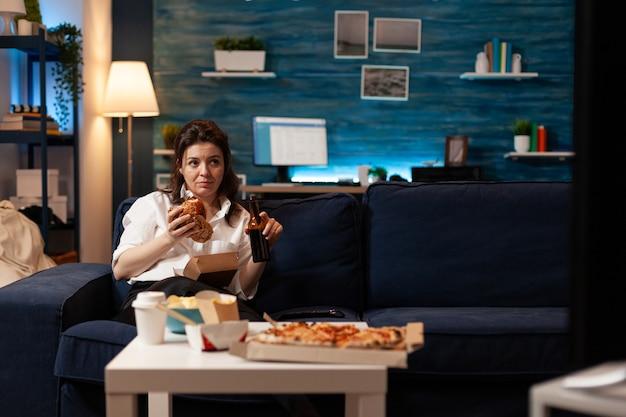 Frau, die sich auf der couch entspannt und eine bierflasche hält, während sie leckeren leckeren burger isst
