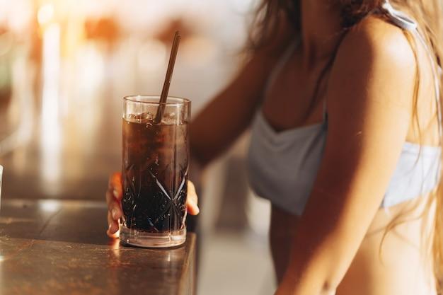 Frau, die sich auf der strandbar ausruht, trinkt einen erfrischenden cocktail