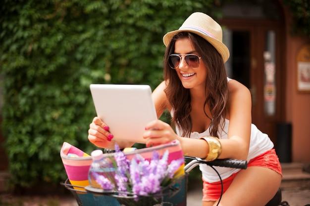 Frau, die sich auf fahrrad stützt und etwas auf tablett überprüft