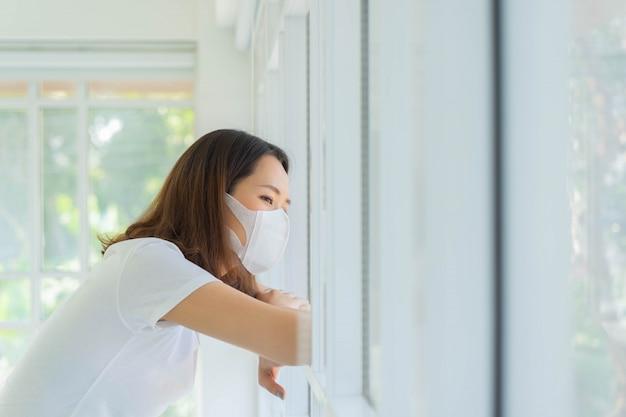 Frau, die sich auf fenster stützt, um nach außen nach quarantänezeitkonzept zu suchen