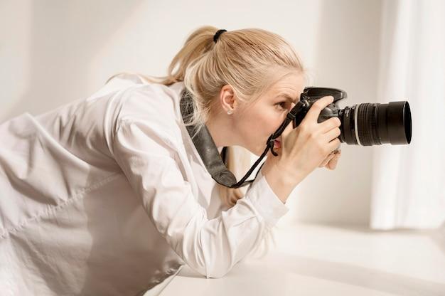 Frau, die sich auf fensterbank stützt und ein foto macht