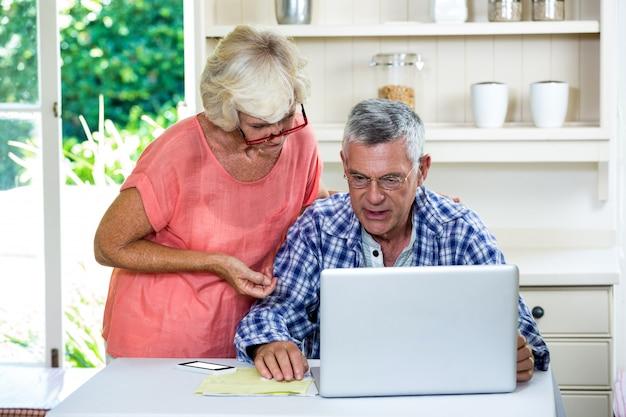 Frau, die sich bei tisch mit älterem mann auf laptop bespricht