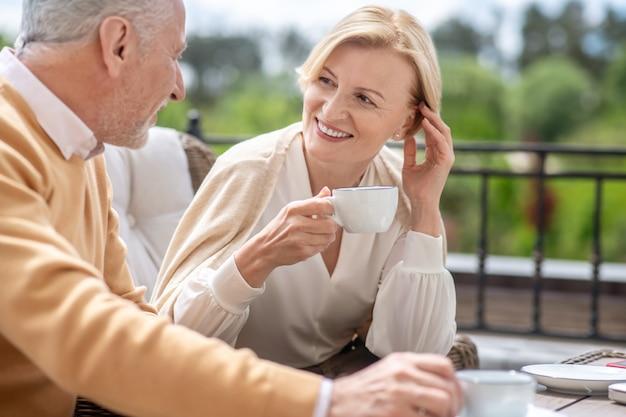 Frau, die sich beim frühstück mit ihrem männlichen ehepartner unterhält