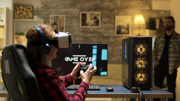 Frau, die sich beim spielen von videospielen mit vr-headset entspannt. spiel vorbei für weibliche spieler. mann im hintergrund.