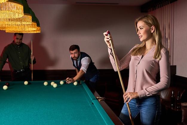 Frau, die sich darauf vorbereitet, professionelles billard im dunklen billardclub zu spielen, verbringen angenehme zeit