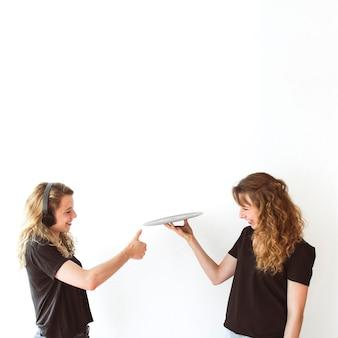 Frau, die sich daumen herauf zeichen zu ihrer balancierenden vinylaufzeichnung der schwester in der hand zeigt