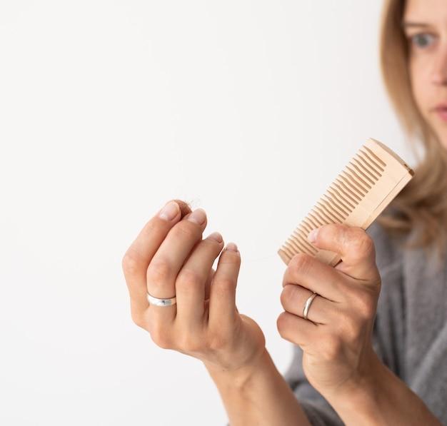 Frau, die sich die haare bürstet, die an haarausfall leidet