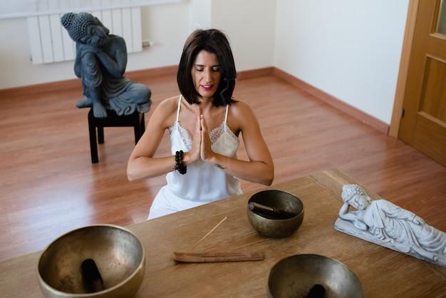 Frau, die sich entspannt auf dem boden sitzt, während sie einen räucherstäbchen verbrennt.