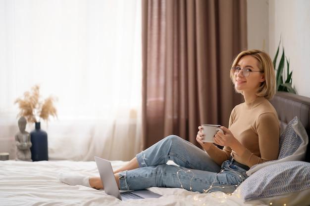Frau, die sich entspannt und tasse heißen kaffee oder tee mit laptop-computer im schlafzimmer trinkt.