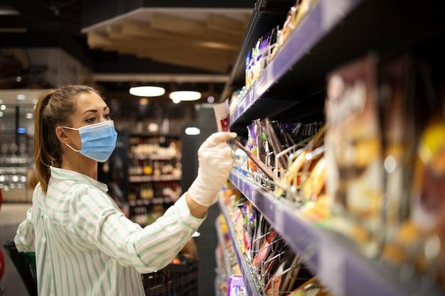 Frau, die sich gegen koronavirus beim einkaufen im supermarkt schützt