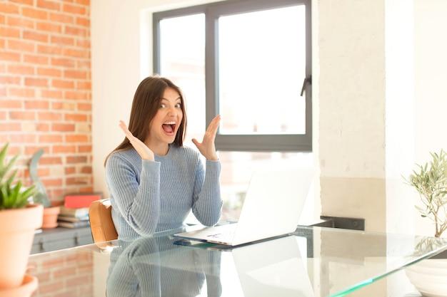 Frau, die sich glücklich, aufgeregt, überrascht oder schockiert fühlt, lächelt und über etwas unglaubliches erstaunt ist