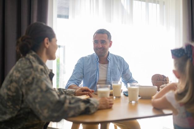 Frau, die sich glücklich fühlt. militärfrau, die sich beim frühstücken glücklich fühlt, wenn sie ehemann und tochter ansieht?