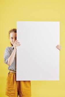 Frau, die sich hinter papierplakat versteckt
