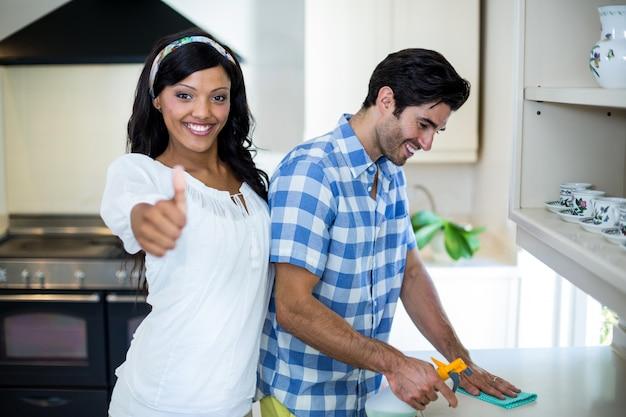 Frau, die sich ihre daumen während mann säubert die küche zeigt