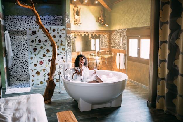 Frau, die sich im hydromassagebad entspannt, das mit schaum bedeckt ist, der auf dem handy spricht