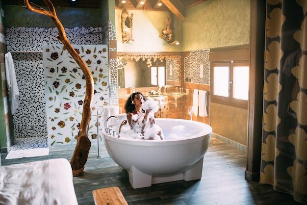 Frau, die sich im hydromassagebad entspannt, das mit schaum bedeckt ist, der musik hört