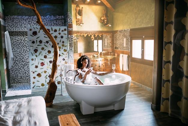 Frau, die sich im hydromassagebad mit schaum mit handy bedeckt