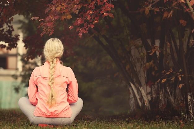 Frau, die sich im park entspannt, rückansicht
