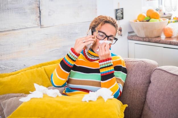 Frau, die sich kalt fühlt, friert, mit serviette in der hand, in decke gewickelt, auf dem sofa sitzend. eine unglückliche, verärgerte, müde frau sitzt zu hause auf einem sofa und ruft mit ihrem telefon an