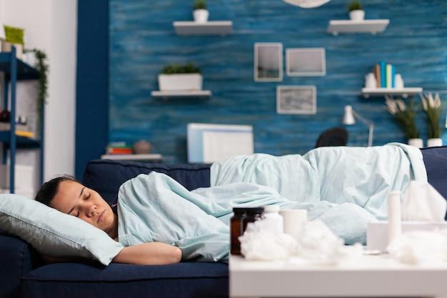 Frau, die sich krank fühlt, wenn sie zu hause auf der couch schläft und sich nach erkältungs- und grippesymptomen erholt. fieber haben und medikamente einnehmen, während sie sich nach einer saisonalen krankheit im schlafzimmer ausruhen