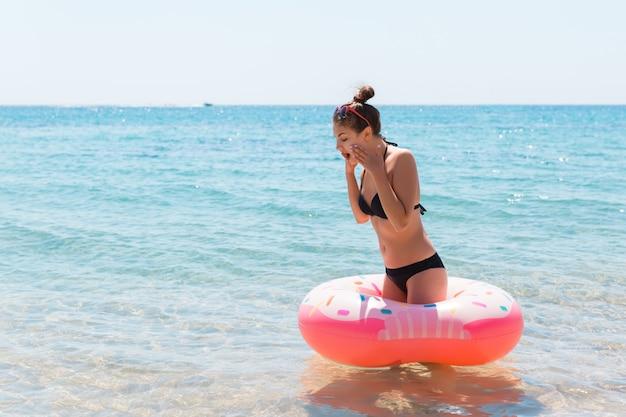Frau, die sich mit aufblasbarem ring am strand entspannt. schockiert oder überrascht mädchen im kalten meer. sommerferien und urlaubskonzept.