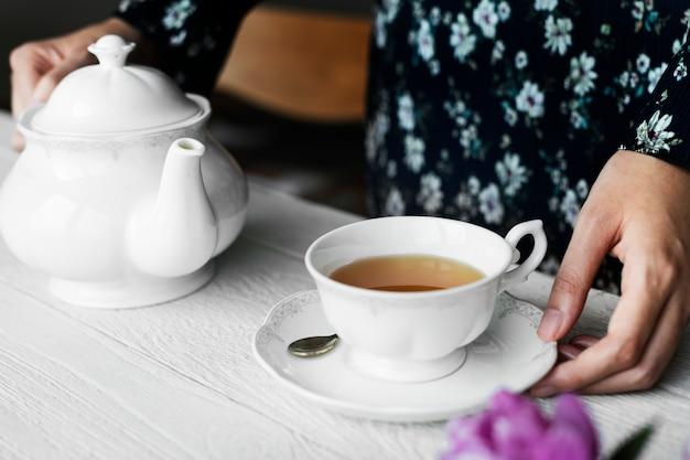 Frau, die sich mit einer schale nettem heißem tee hilft