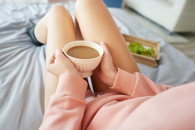 Frau, die sich mit einer tasse kaffee am morgen aufwärmt