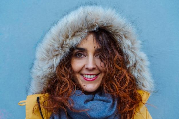 Frau, die sich mit kapuze vor winterregen schützt