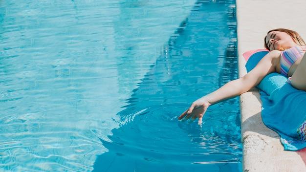 Frau, die sich neben pool entspannt