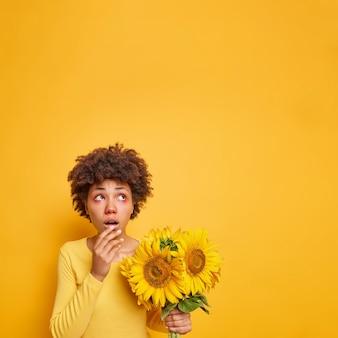Frau, die sich oben mit nachdenklichem ausdruck konzentriert, hält sonnenblumen hat rote juckende augen, die allergisch gegen pollen sind, die auf gelb isoliert sind?