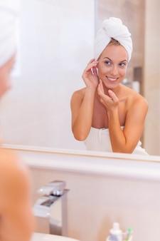 Frau, die sich spiegelbild im spiegel nach der dusche schaut